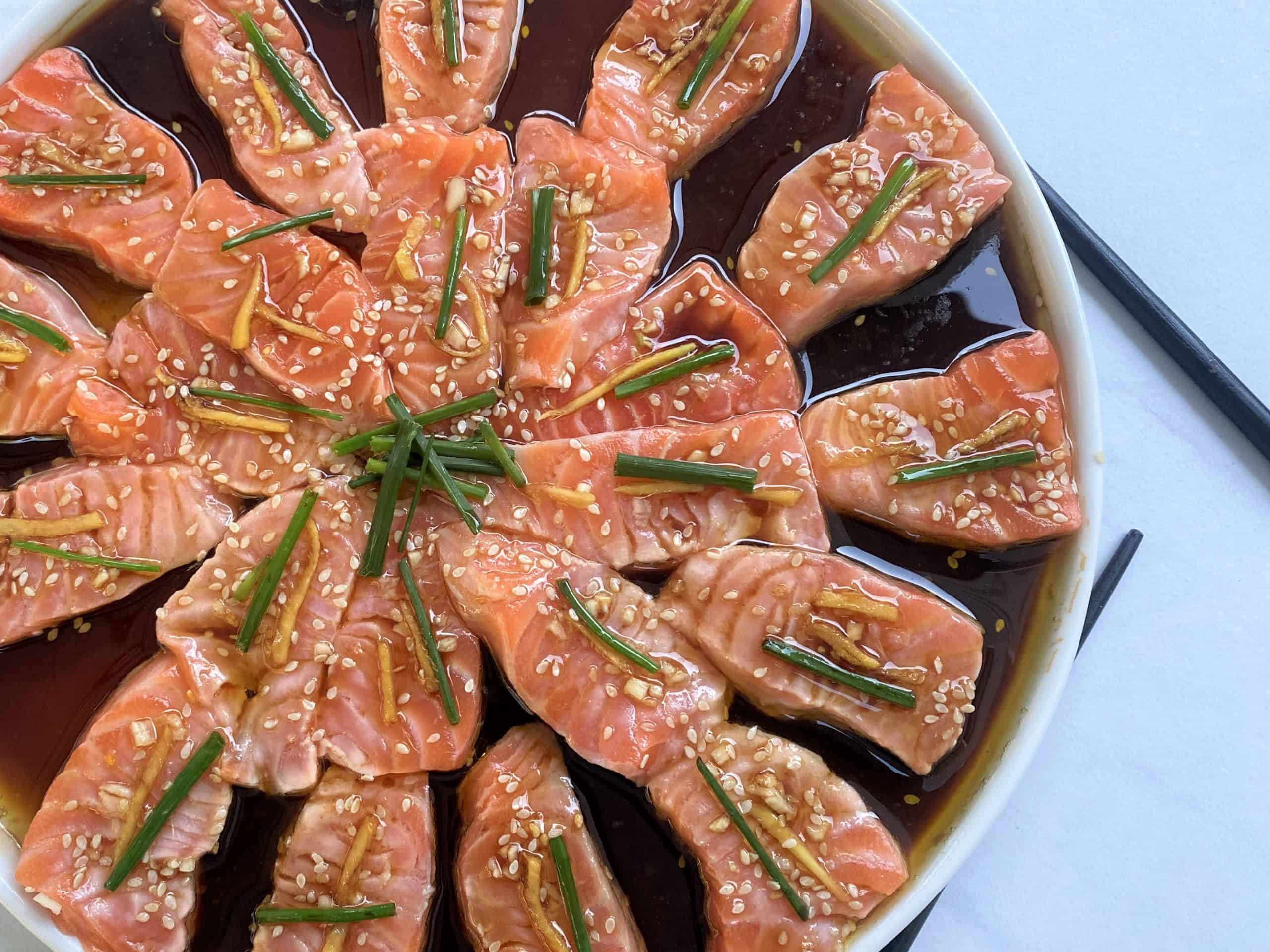 Nobu's new style sashimi made with salmon.. Sliced salmon placed circularly on a plate with toppings.