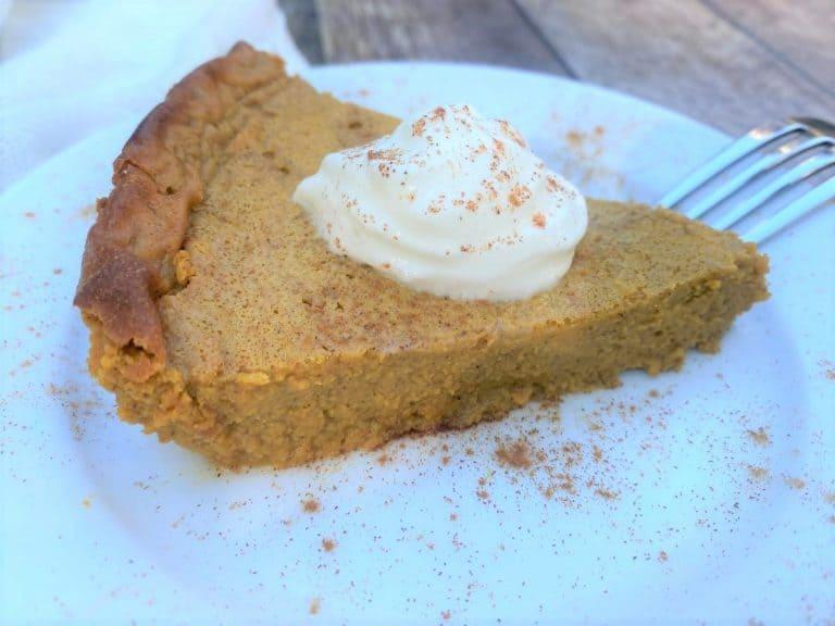 Slice of crustless keto pumpkin pie with sugar-free whipped cream on top