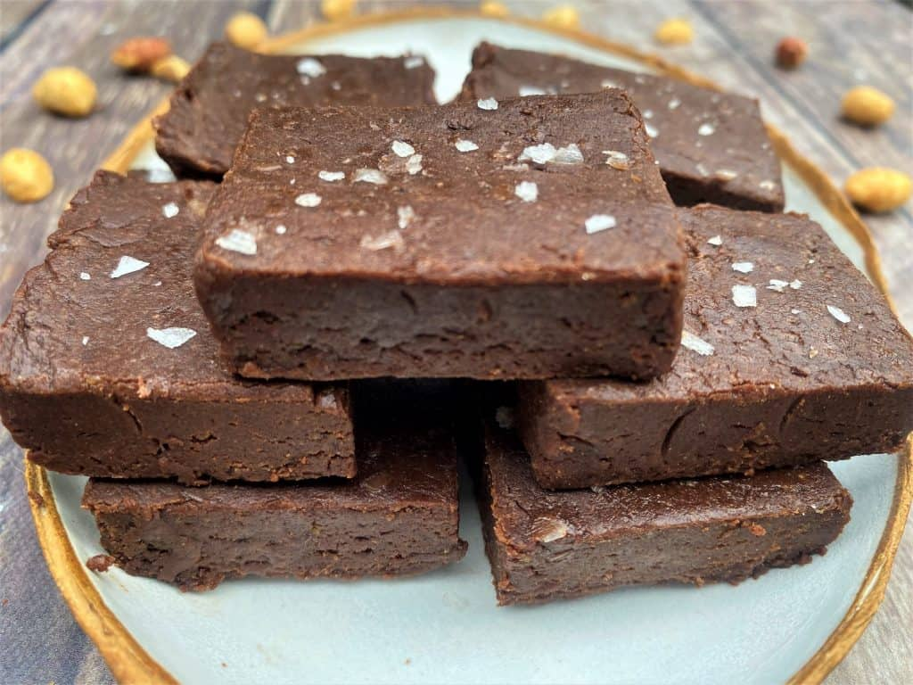 Side view of cut high-protein chocolate peanut butter fudge on a plate.