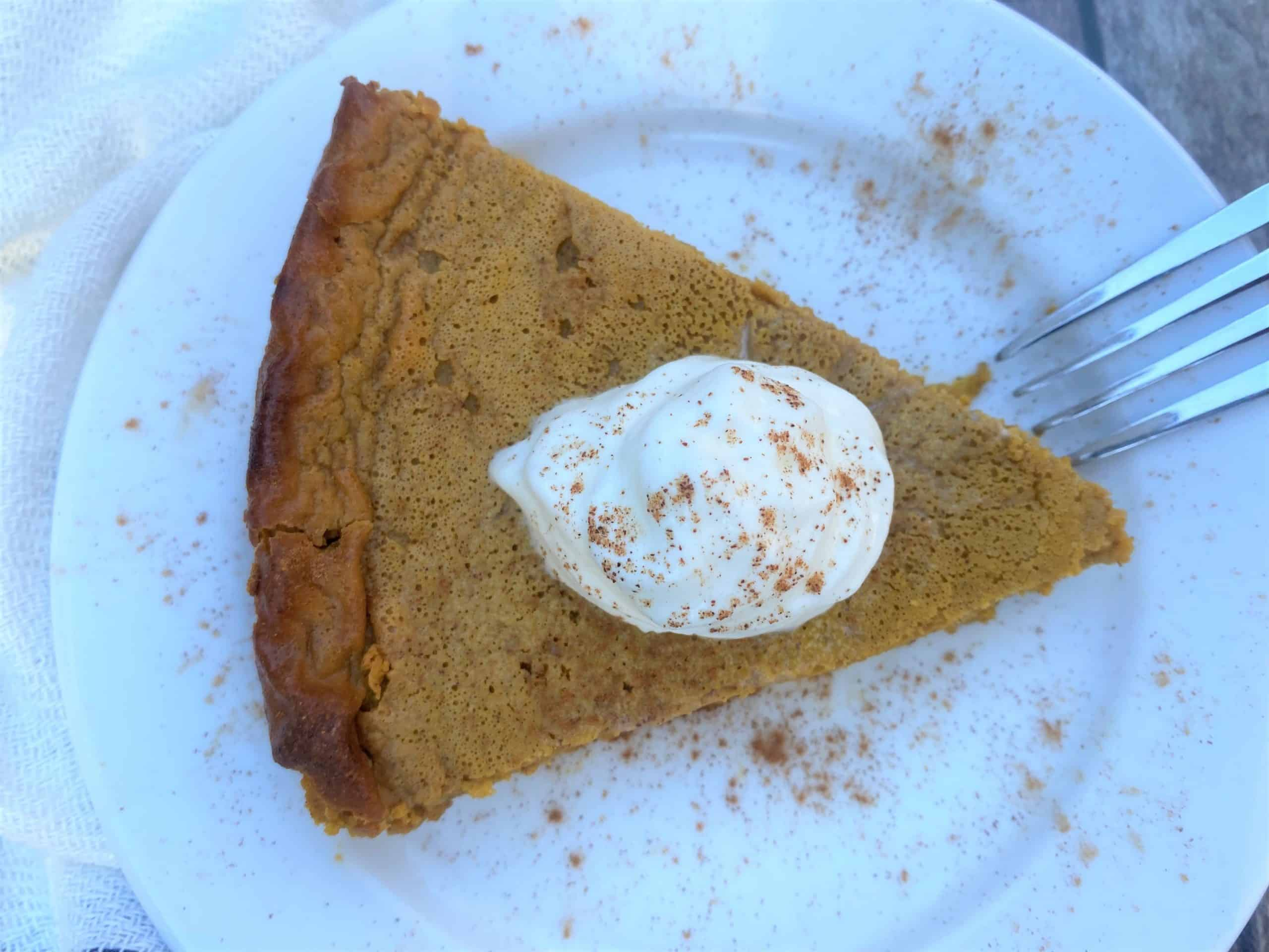 Birds eye view of keto pumpkin pie slice with sugar-free whipped cream on top.