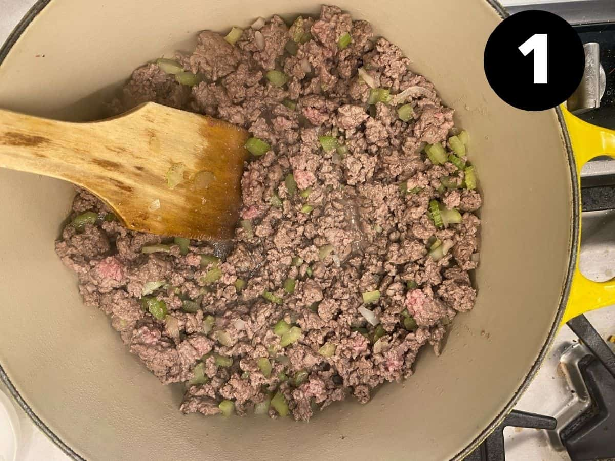 Cooked beef with diced celery and onions in a large pot being stirred.
