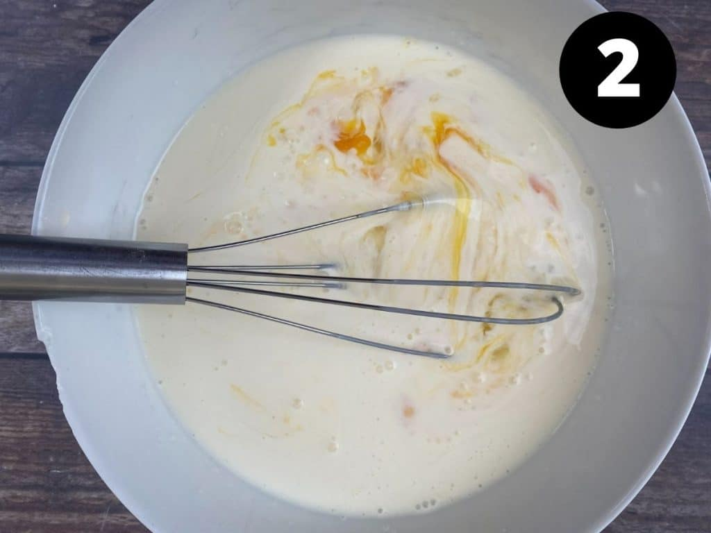 Mixing bowl with eggs and heavy cream being mixed. Labeled step 2.