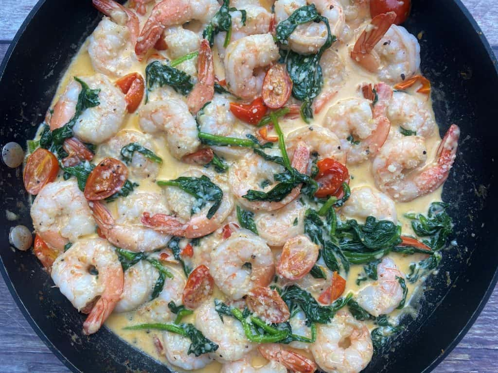 cooked shrimp with spinach, grape tomatoes, in heavy Parmesan sauce in a cast iron pan.
