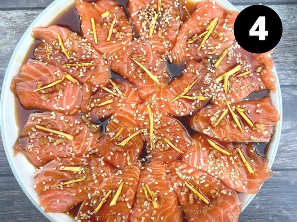 Salmon sashimi in a circular design with soy mixture, ginger, garlic and sesame seeds.