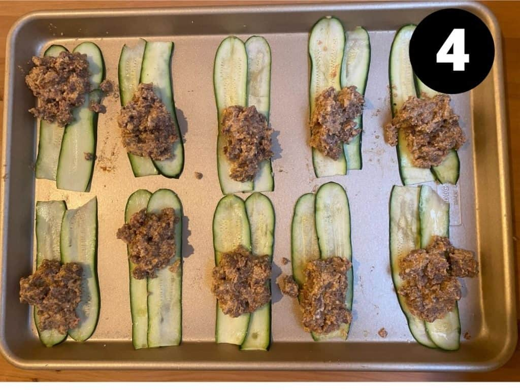 Sets of two zucchini strips with a scoop of meat mixture on top.