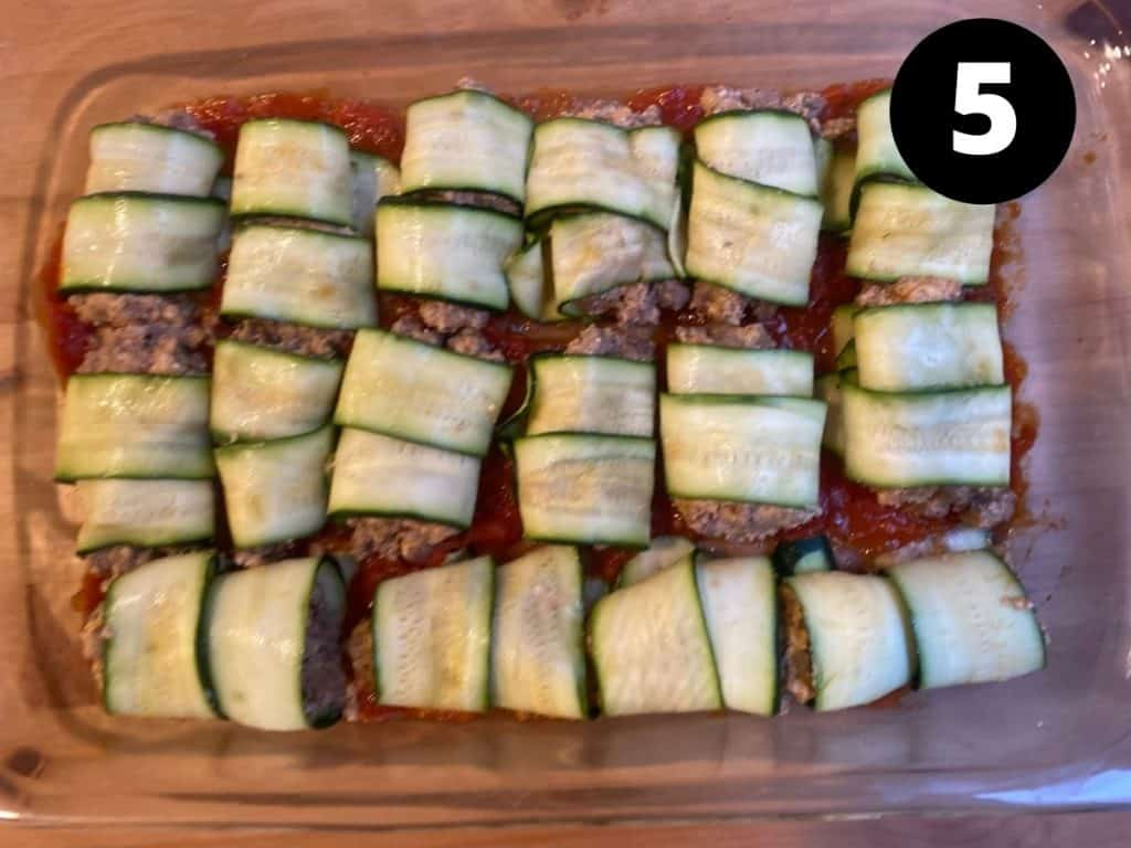 Sets of rolled zucchini strips with meat mixture in middle.