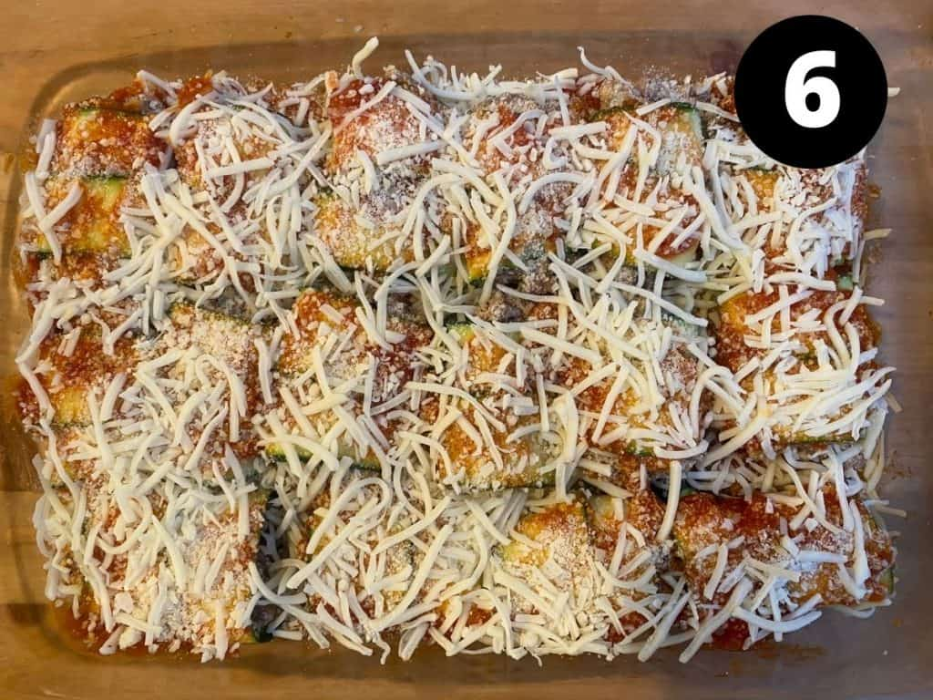 Zucchini rolls with pasta sauce on top and shredded cheese